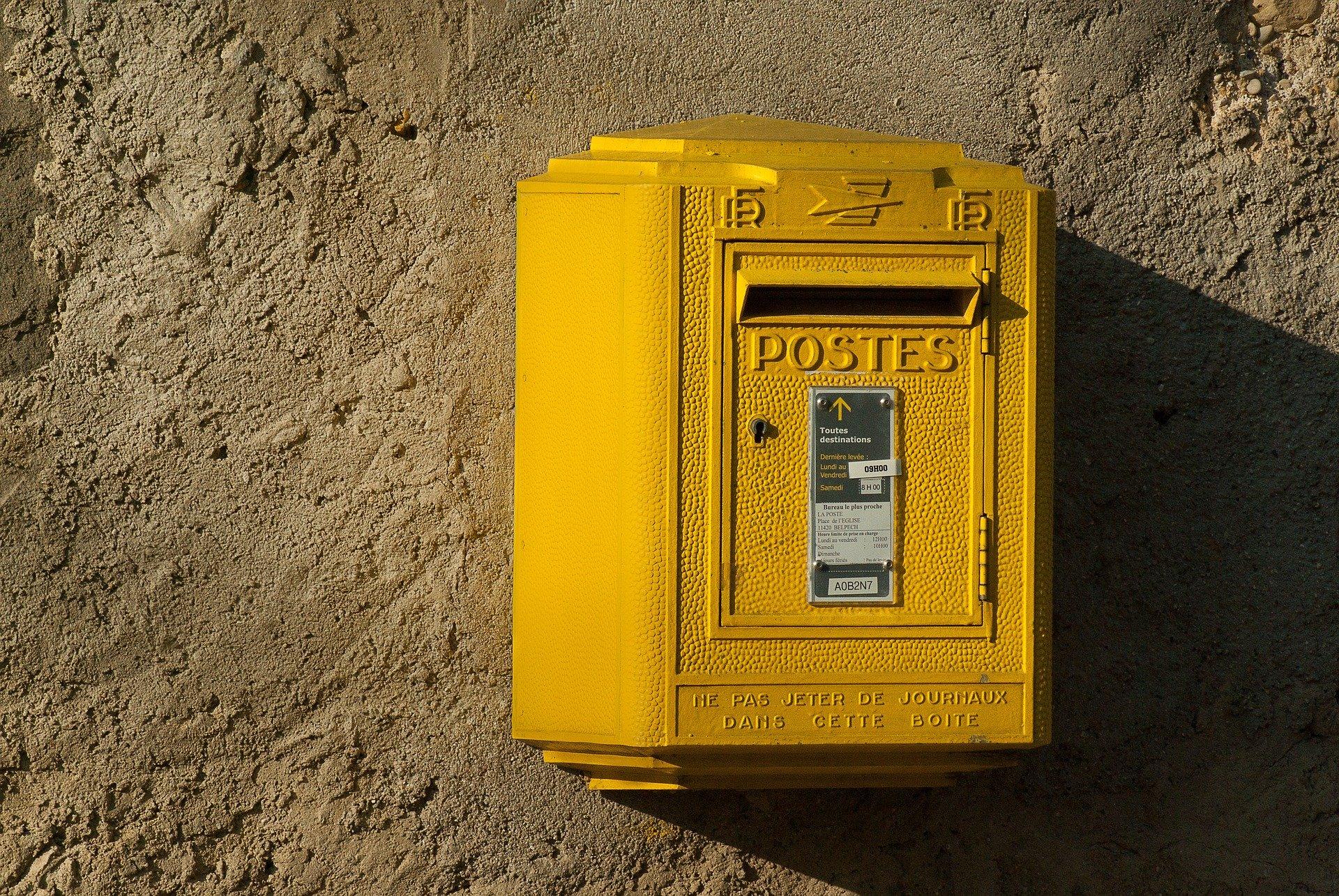 Boîte postale jaune sur un mur