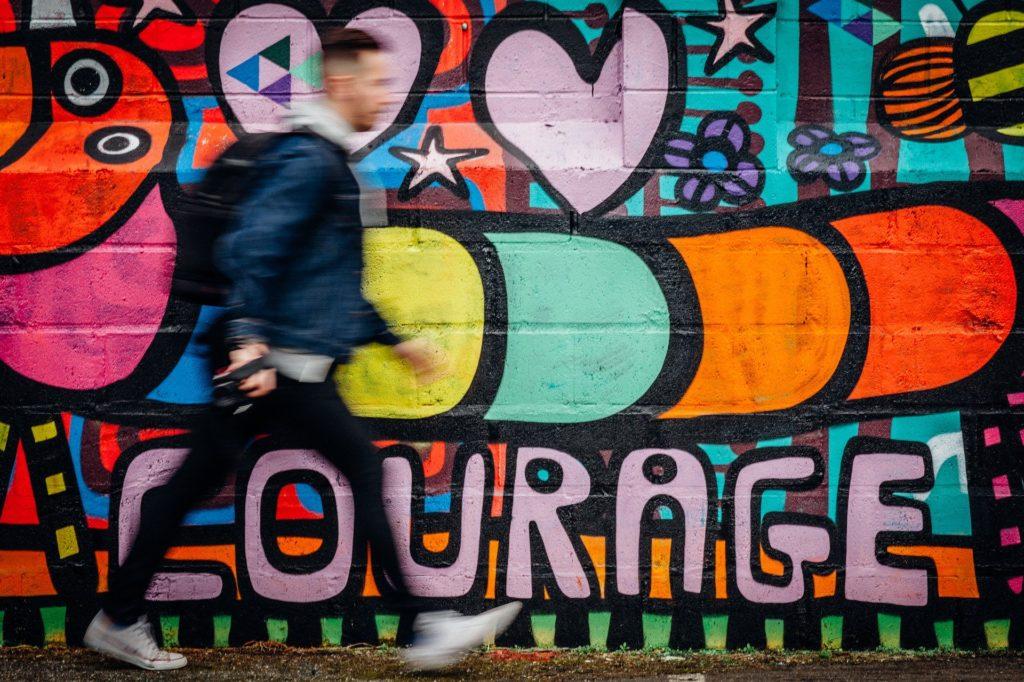 homme passant devant un mur ou se trouve un tag courage